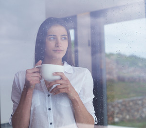 Young woman drinking coffee looking out window