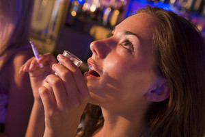 Young woman drinking shots and smoking at a nightclub