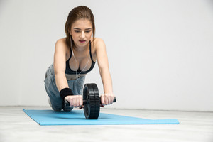 Young woman exercising fitness workout abdominal wheel