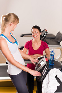 Young woman friends exercising in fitness center on treadmill machine