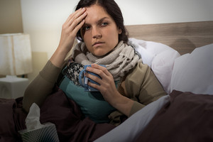 Young woman having flu sitting in bed