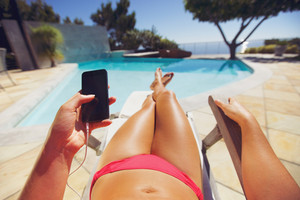 Young woman holding a smart phone by the pool. Female model relaxing on a deckchair using mobile phone.
