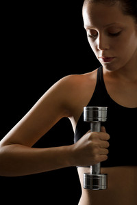 Young woman holding fitness dumbbell on black background