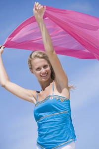 Young woman holding pink wrap against blue sky