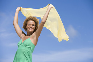 Young woman holding scarf against blue sky