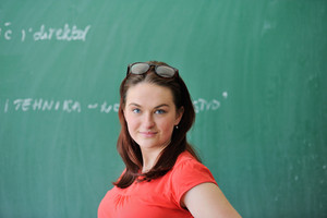 Young woman in red shirt in front of school blackboard