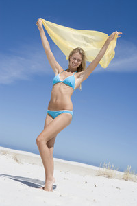 Young woman in swimwear at beach holding wrap