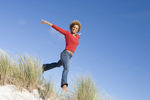 Young woman jumping amongst sand dunes against blue sky
