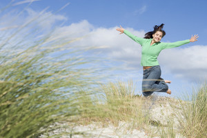Young woman jumping in air amongst sand dunes