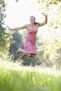 Young woman jumping in summer meadow