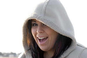 Young woman laughing while wearing a hooded winter coat.