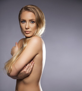 Young woman looking at camera while covering her naked body. Copy space right. Beautiful model with bond hair.