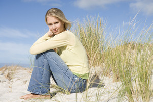 Young woman looking thoughtful amongst sand dunes