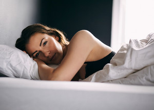Young woman lying in her bed under duvet looking at camera. Female model in lingerie sleeping in bedroom.
