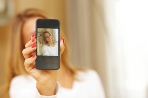Young woman making self-photo on smartphone