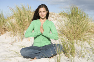 Young woman meditating amongst sand dunes looking to camera