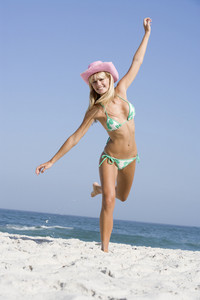 Young woman on beach holiday wearing cowboy hat