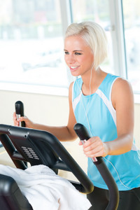 Young woman on fitness machine cardio exercise at sport club