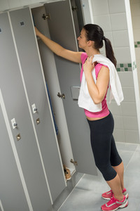 Young woman opening locker in changing room at gym