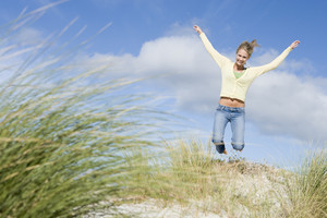 Young woman performing mid-air jump amongst dunes