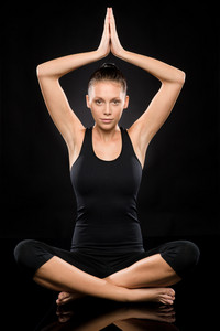 Young woman performing yoga with raised clasped hands lotus position