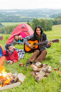 Young woman playing guitar beside camping friends lying in tents