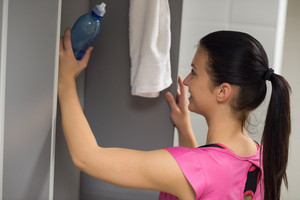 Young woman putting water bottle in locker at gym's changing room