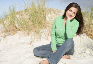 Young woman relaxing amongst dunes looking to camera