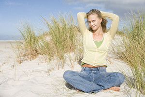 Young woman relaxing amongst dunes to camera