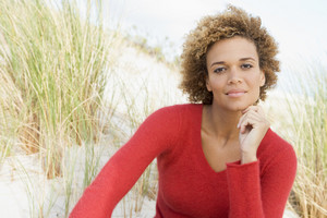 Young woman relaxing at beach looking to camera