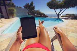 Young woman relaxing on a lounge chair using a tablet PC near the pool. User POV. Female model sitting on a deckchair holding digital tablet.