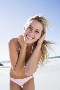 Young woman relaxing on beach wearing bikini