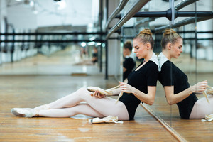 Young woman resting on the floor in ballet class
