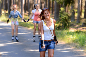 Young woman roller skating outdoors with friends summer sport