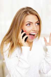 Young woman screaming in amusement on phone