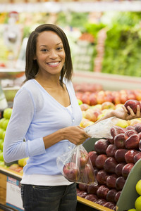 Young woman shopping for fresh produce in supermarket