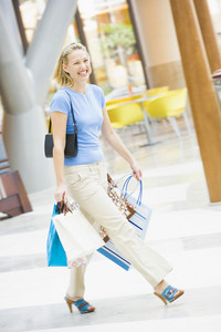 Young woman shopping in mall carrying bags