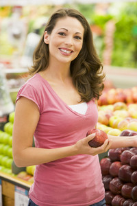 Young woman shopping in produce department of supermarket