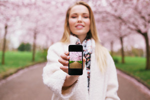 Young woman showing a photograph on her smart phone at you. Female at spring park displaying images on her mobile phone.