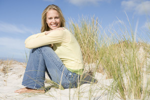Young woman sitting amongst dunes smiling at camera