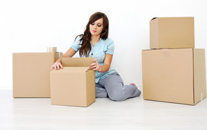 Young woman sitting and opened cardboard box