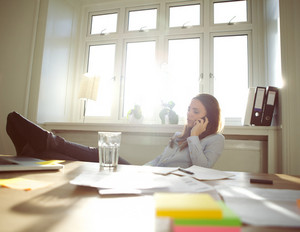 Young woman sitting at her table with legs on desk talking on mobile phone. Caucasian businesswoman using cell phone while relaxing at her desk. Female working from home office.
