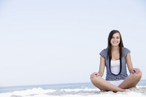 Young woman sitting on beach with ocean behind
