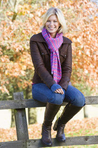 Young woman sitting on fence with autumn woodland behind