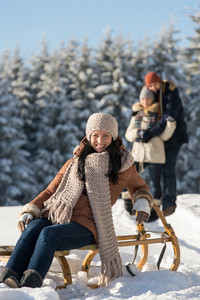 Young woman sitting winter wooden sledge friends in sunny background