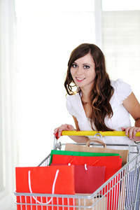 Young woman smiling with shopping cart