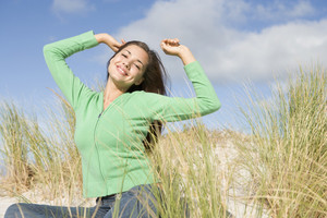 Young woman stretching in dunes to camera
