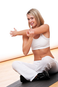 Young woman stretching on black mat