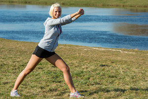 Young woman stretching outdoors before jogging workout by park lake