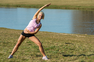 Young woman stretching outdoors before jogging workout sunny park